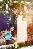 浇灌与蓝色喷壶的妇女玫瑰色花在庭院里 免版税图库摄影
