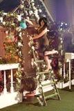 浇灌与蓝色喷壶的妇女玫瑰色花在庭院里 图库摄影
