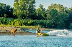 浇灌乐趣和kiteboarding用Ada Bojana,黑山,有狗的 免版税库存照片