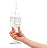 浇灌倾吐入充分的酒杯在妇女的手上 免版税库存图片