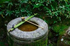 浇灌在一个石水池的浸染工在十三弦琴在寺庙在京都 免版税库存图片