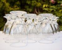 浇灌在一张白色桌布排队的酒杯 免版税库存图片