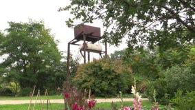 浇灌在庭院里的植物花的生锈的水储水池坦克 股票录像