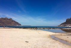 浇灌在海滩、海、天空和山 库存图片