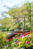浇灌在石瓶子在庭院里 库存图片