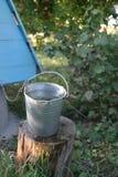 浇灌在金属桶在井附近 免版税库存图片