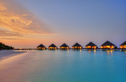 浇灌在马尔代夫常去之岛上的别墅日落的 库存照片