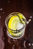 浇灌在玻璃的飞溅与柠檬切片和冰块,在木桌上,顶视图 免版税库存图片