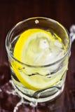 浇灌在玻璃的飞溅与柠檬切片和冰块,在木桌上 图库摄影