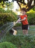 浇灌庭院的男孩 免版税图库摄影