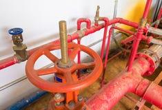 浇灌有工业修造的尘土肮脏的里面的阀门管道系统老大配管红色 免版税库存照片
