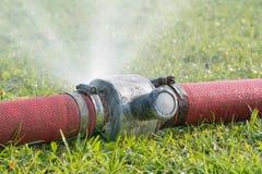 浇灌漏从在一个工业水管的孔 库存图片