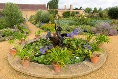 浇灌特点并且在Ilminster萨默塞特有庭院的英国英国附近从事园艺巴林顿法院在夏天阳光下 免版税库存照片
