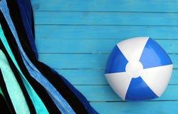 浇灌球和镶边海滩毛巾在蓝色木板条 免版税库存图片