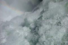 浇灌生泡沫从与一条微弱的彩虹的瀑布 库存图片