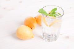 浇灌用柠檬和薄菏在一块玻璃在台式viewew 免版税库存图片