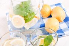 浇灌用柠檬和薄菏在一块玻璃在台式viewew 库存图片