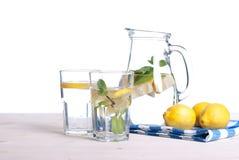 浇灌用柠檬和薄菏在一块玻璃在i桌侧视图  库存图片
