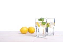 浇灌用柠檬和薄菏在一块玻璃在i桌侧视图  免版税库存照片