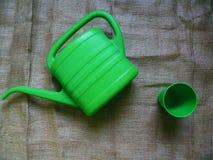 浇灌的花和一块绿色塑料玻璃的绿色喷壶 免版税库存照片