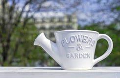 浇灌的花和植物的白色陶瓷喷壶春天背景的 库存图片
