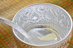 浇灌碗在席子的做的ââof银 免版税库存图片