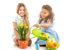 浇灌花和使用在地板上的两个小女孩 库存图片