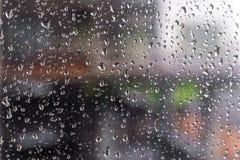 浇灌雨水滴在玻璃的有室外背景 免版税库存图片