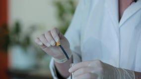 测试一种化学制品的酸碱度的在试管的人佩带的手套 股票录像