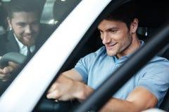 测试一辆新的汽车的年轻微笑的夫妇,当坐里面时 库存照片