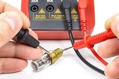 测试与一个多用电表的老电灯泡在白色背景 免版税库存图片