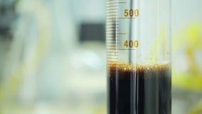 测试中心的女性在油库的倾吐生物燃料入从瓶的烧杯 股票录像
