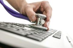 测试有听诊器的一个计算机键盘 免版税库存照片