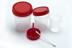 测试的,尿透明塑胶容器 分析的银行 有红色盒盖的空的容器 免版税库存照片