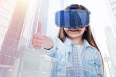 测试VR耳机和显示的微笑的女孩赞许 库存照片