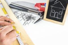 测量一个木板条的建造者手 免版税库存照片