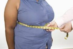 测量一名肥胖妇女的腹部的手 免版税库存照片