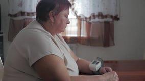 测量与数字血压计的成熟肥胖妇女压力,当坐在桌上时 资深妇女保重 影视素材
