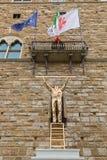 测量云彩人的雕象,站立在梯子上面 库存照片