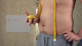 测量他的腰部,一个大啤酒肚,一种健康生活方式吃苹果的一个油脂人 影视素材