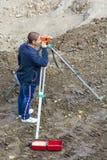 测量员在水平帮助下做测量 工作场所 免版税图库摄影