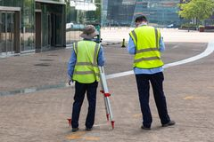 测量员建造者工程师与勘测在三脚架运输设备的设备经纬仪一起使用在工地工作 库存照片