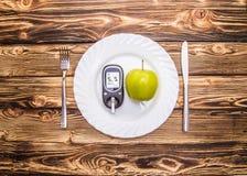 测量在板材,正确健康饮食的概念的血糖的苹果计算机和glucometer 库存图片