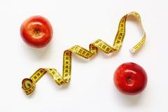 测量在白色背景的磁带和新鲜水果苹果 损失重量,亭亭玉立的身体,健康饮食概念 免版税图库摄影