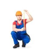 测量墙壁的建筑工人 免版税库存照片