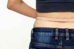 测量她的有一卷测量的磁带的美丽的女孩腰部 库存照片