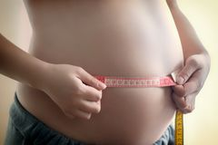 测量她的有一卷测量的磁带的,关闭的怀孕的女孩胃 免版税库存图片