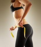 测量她的有卷尺的女孩腰部 免版税库存图片