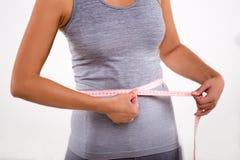 测量她的有卷尺的愉快的健身女孩腰部 库存图片