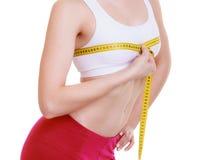 测量她的胸象大小的健身女孩运动的妇女被隔绝 免版税库存图片